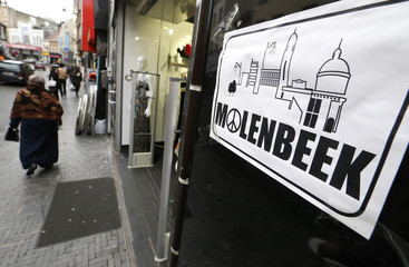 """File photo of a placard reading Molenbeek with a """"peace and love sign"""" being seen on a shopping street in the suburb of Molenbeek, Brussels"""
