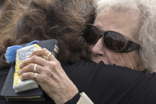 Women hug at open air Sunday church service four days after deadly fertilizer plant explosion in the town of West