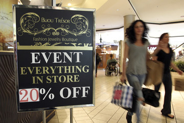 People carry shopping bags as they walk past a sale sign at the Beverly Center mall Los Angeles
