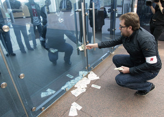 An activist from Molodaya Gvardia, the youth movement of the political party United Russia, tries to force money under the door of the headquarters of Russian oil company Lukoil to protest against high oil prices during a meeting in central Moscow