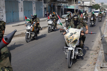 Hamas militants ride motorcycles as they patrol a street on the first anniversary of the eight-day conflict with Israel, in Rafah in the southern Gaza Strip