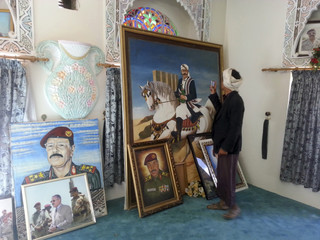 A resident takes pictures of a painting in a room inside a house of Yemen's dissident General Ali Mohsen al-Ahmar after Shi'ite Houthi rebels took control of it in Sanaa