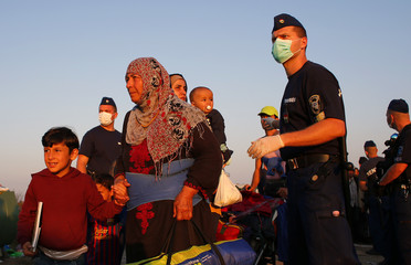 Migrants pass between policemen at a collection point near the Serbian-Hungarian border in Roszke
