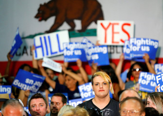 Supporters look on as U.S. Democratic presidential candidate Hillary Clinton delivers a speech during a campaign stop in Fresno, California