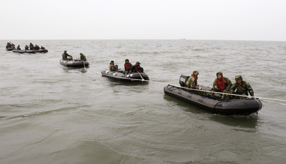 South Korean Navy's Ship Salvage Unit members on rubber boats search possible survivors and bodies from a sunken naval ship Cheonan off Baengnyeongdo