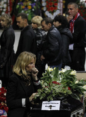 Relative grieves on coffin of Latvian hockey player Skrastins during funeral ceremony at Arena-2000 in Yaroslavl