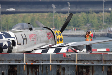 A worker photographs the wreckage of a vintage P-47 Thunderbolt airplane that crashed in the Hudson River in New York