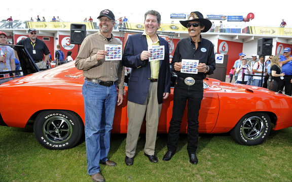 U.S. Postmaster General Donahoe stands with racing legend Richard Petty and his son Kyle Petty as they hold the new Muscle Cars Forever stamps at the Daytona International Speedway
