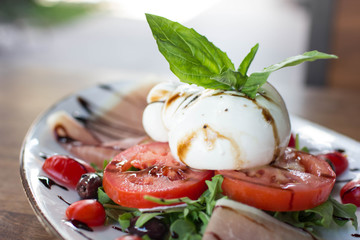 Burrata Mozzarella Caprese accompanied by olives, prosciutto, and arugula