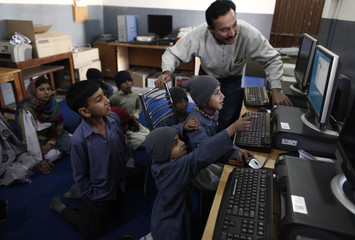 Students from underprivileged background learn to use a computer at Mashal School on the outskirts of Islamabad