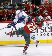 Vancouver Canucks' Tanev collides with Minnesota Wild's Clutterbuck during the third period of their NHL hockey game in St. Paul
