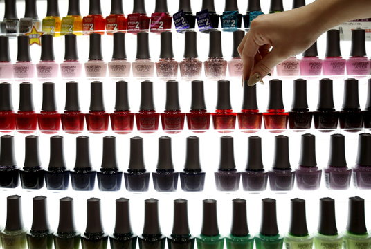 A shop clerk adjusts a bottle of manicure displayed at an exhibition and sale during Tokyo Nail Expo 2015 in Tokyo