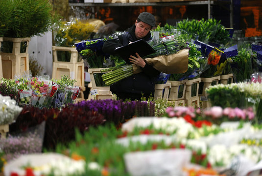 A customer checks his shopping list as he holds a bouquet at New Covent Garden wholesale flower market on the eve of St Valentine's Day in London