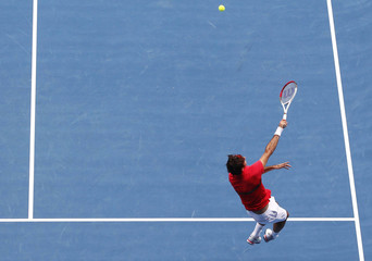 Federer of Switzerland jumps to make a smash against Karlovic of Croatia at the Australian Open tennis tournament in Melbourne