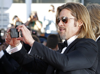 Cast member Pitt uses his mobilephone on the red carpet ahead of the screening of the film Killing Them Softly in competition at the 65th Cannes Film Festival