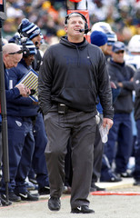 Tennessee Titans head coach Mike Munchak checks the replay against the Green Bay Packers during the first half of a NFL football game in Green Bay