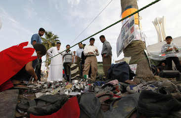A boy looks at shoes and ammunition shells left by riot police at Pearl Square in Manama
