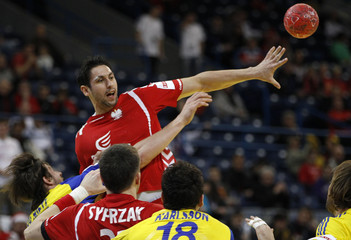 Zaremba of Poland is challenged by du Rietz of Sweden during their Men's European Handball Championship main round match in Belgrade