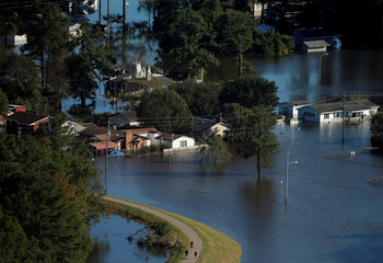 People are seen walking on an elevated path as flood waters surround them after Hurricane Matthew in Lumberton