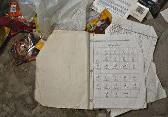 A notebook, with Arabic alphabets, sits on a bed of the apartment rented to suspects Nuttall and Korody in Surrey