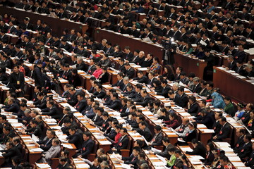 Delegates follow speech at the Great Hall of the People during the third plenary session of the National People's Congress, in Beijing