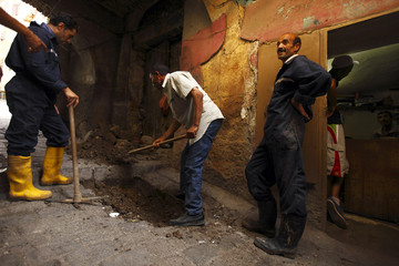 Workers try to find the location of a water leak at the old city in the eastern province of Constantine
