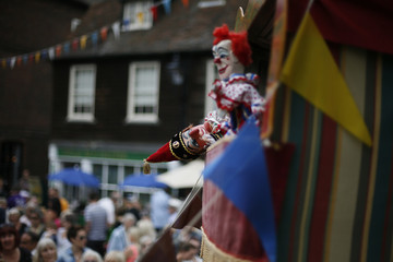 "Punch and Judy ""professor"" Robert Styles performs a show during a Dickens Festival in Rochester, southern England"