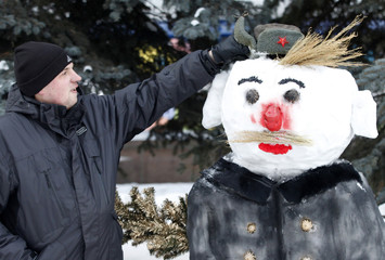"""A man sculpts a """"Military snowman"""" during the """"Parade of snowmen"""" annual city competition at the Central park of Krasnoyarsk"""