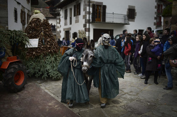 Masked men lead a donkey through the streets during carnival celebrations in Zubieta