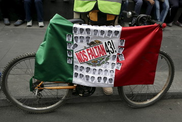 A Mexican flag and some pictures of the 43 missing students of Ayotzinapa College are seen hanging on a bicycle during a demonstration in Mexico City