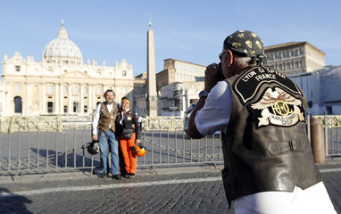 A Harley-Davidson biker from the Lyon Chapter France takes pictures of his friends in front of St. Peter's square during the Harley-Davidson 110th Anniversary Party in Rome