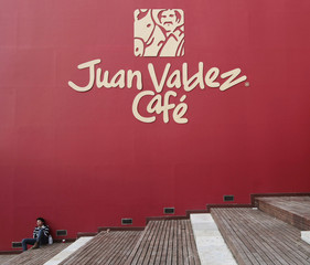 A student sits in front of a wall painted with a logo of the Juan Valdez cafe, north of Bogota