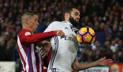 Real Madrid's Nacho in action with Atletico Madrid's Fernando Torres