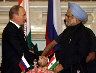 India's PM Singh shakes hands with his Russian counterpart Putin in New Delhi