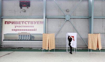 A woman leaves a voting booth before casting her ballot at a polling station during the presidential elections in the southern city of Stavropol