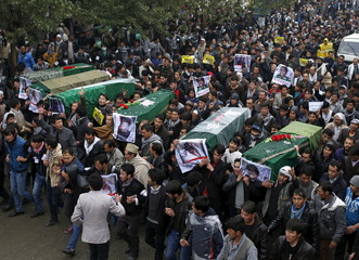 Men carry coffins for the seven people who were killed by unknown militants, heading towards the presidential palace, during a protest procession in Kabul, Afghanistan