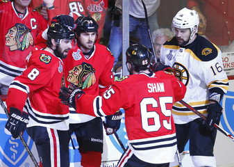 Blackhawks' Bolland celebrates his goal with teammates Leddy and Shaw as Bruins' Daugavins skates past during the third period in Game 1 of their NHL Stanley Cup Finals hockey series in Chicago