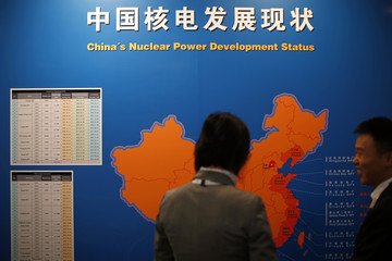 Visitors look at a map which shows China's nuclear power development status at the World Nuclear Exhibition 2014 in Le Bourget