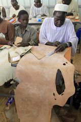 Shoemakers cut leather at a workshop in Abu Zaid market in Khartoum