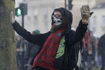 A masked protester taunts French riot police during clashes at a demonstration to mark the one-year anniversary of a protest march in 2014 which ended in violence, in Nantes