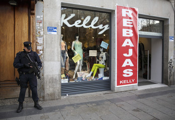 A riot policeman holding a weapon stands next to a cloth store announcing sales in Madrid