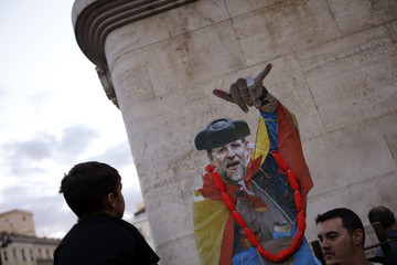 A boy looks at a satirical cutout of Spanish Prime Minister Rajoy during a demonstration calling for the resignation of Rajoy, in Madrid