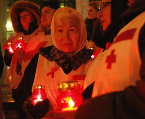 People hold candles as they gather to mark the upcoming World AIDS Day in Kiev