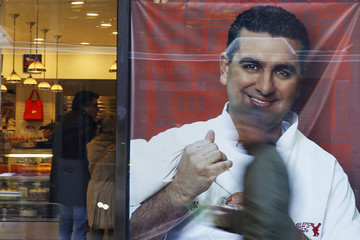 People walk by a photo of celebrity chef Buddy Valastro outside his 'Cake Boss' cafe in New York