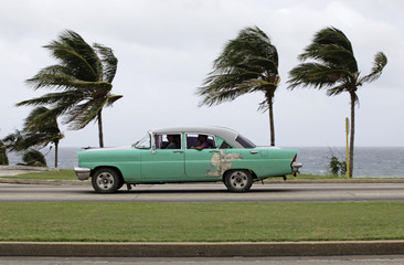 People ride a taxi as strong winds blow palm trees in Havana