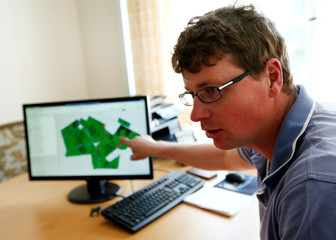 "Juergen Schwarzensteiner, factory manager of  ""Poschinger Bray'sche Gueterverwaltung"", explains the ""talking fields"" biomass map on a computer in Irlbach"