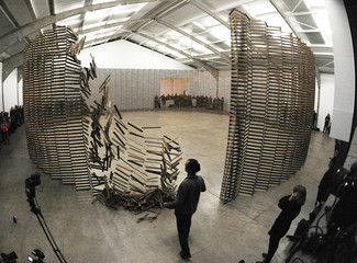 British artist Aeneas Wilder (C) kicks down his installation  'Untitled # 155'  consisting of 10,000 wooden slats, in a performance at the Yorkshire sculpture park near Barnsley
