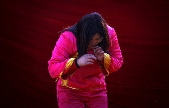 A woman brings a live snake back up after she swallowed it as she performs on a small stage showcasing acts of magic and feats of unusual physical abilities at the temple fair in Ditan Park