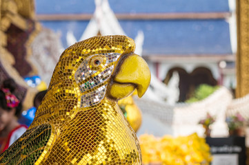 Closeup beautiful parrot bird statue by yellow tiles for decorate in temple of thailand background