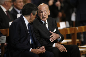 Former French President Valery Giscard d'Estaing speaks with former French prime minister and deputy Francois Fillon before a mass at the Notre-Dame Cathedral in Paris